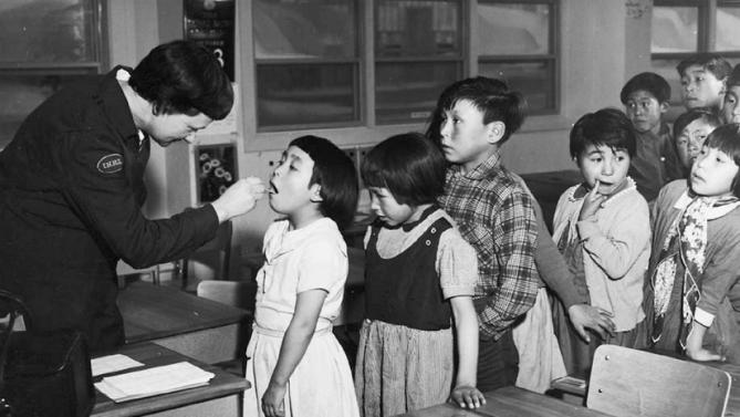Archive photo of Nurse Desrochers checking a girl's throat while other children wait in line, at the Frobish Bay Federal Hostel in Iqaluit
